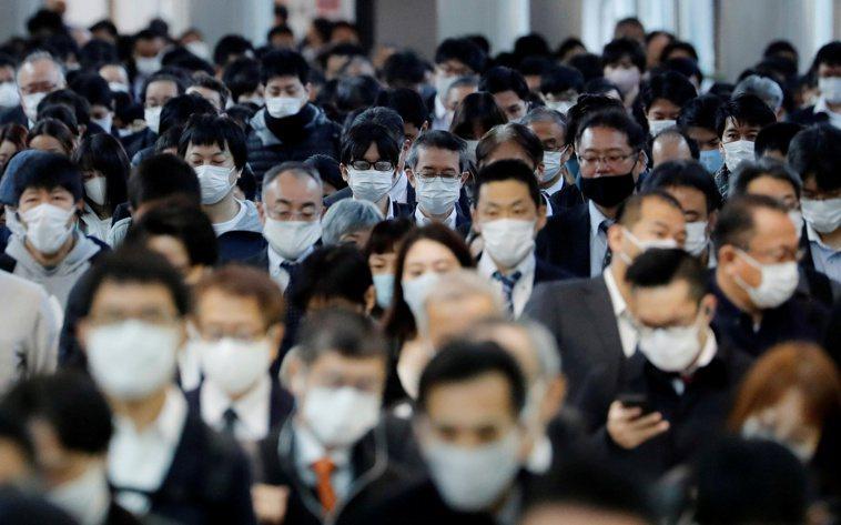 日本東京品川車站,擠滿戴著口罩的通勤上班族。路透