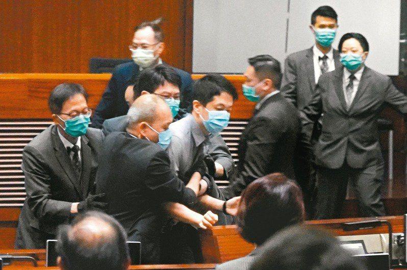 圖為當時許智峯(右二)投擲惡臭物被逐出會議廳。(中新社)