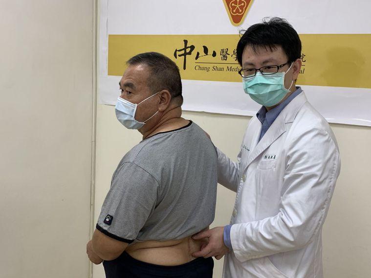 醫師楊宗熹(右)指林姓病患( 左)腰椎椎間盤突出,造成急性下肢麻痛。圖/中山附醫...