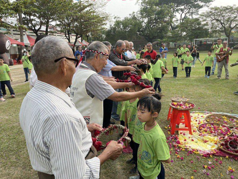 台南新化口埤實驗小學今天慶祝百年校慶,西拉雅長老為小朋友戴上花圈,象徵傳承。圖/校方提供