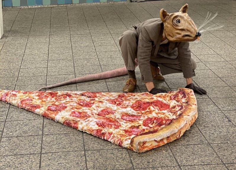 美國紐約市近日出現一名表演藝術家扮成「巨鼠」出沒在大街小巷引發話題,近期他更重現「地鐵鼠咬披薩」的名場面,影片在網路上爆紅。畫面翻攝:Jonothonlyons.com
