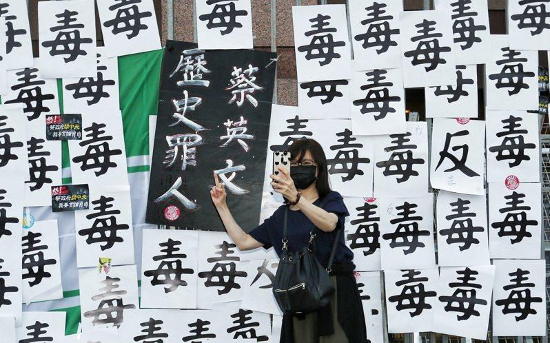 秋鬥遊行於今日下午登場,遊行民眾與貼滿「毒」的民進黨黨部門口合影。記者曾原信/攝影