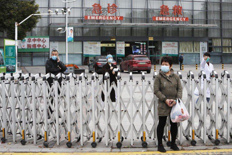 上海新確診病例中包括一名浦東醫院護理師,浦東醫院因此實行封閉管理。圖為醫護人員和患者家屬等待家人送生活用品。(中新社)