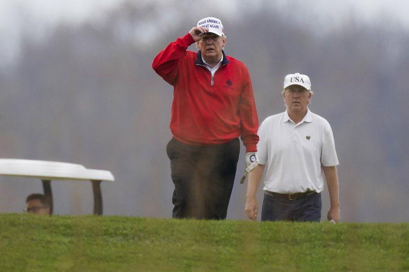 美國總統川普(左)21日在維吉尼亞州自家高球場打球。美聯社