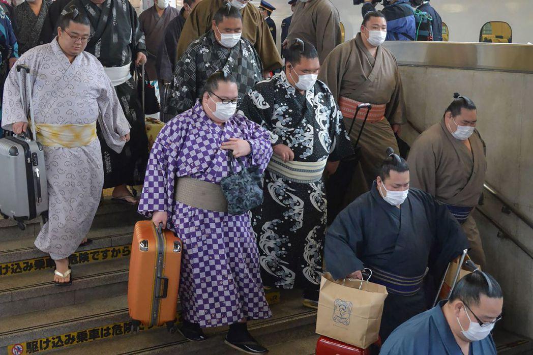 一群戴口罩的相撲力士今年二月抵達新大阪車站後拿著行李下樓梯。(法新社)