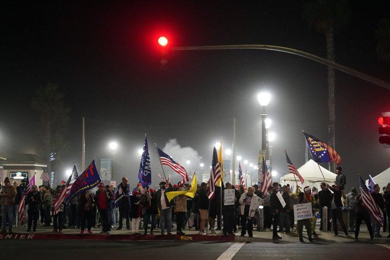 美國加州為了防疫廿一日起實施宵禁,部分反對防疫限制的民眾廿一日在杭亭頓海灘遊行抗議。(美聯社)