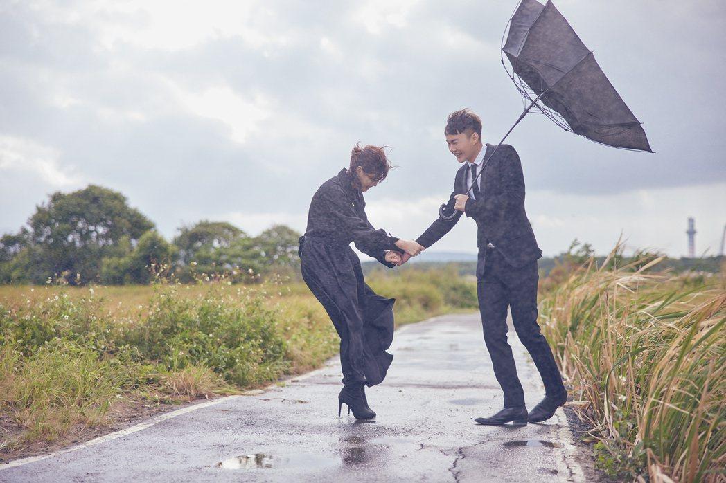 許富凱(右)和方馨拍攝時遭遇強風來襲,雨傘開花。圖/凱聲影藝提供