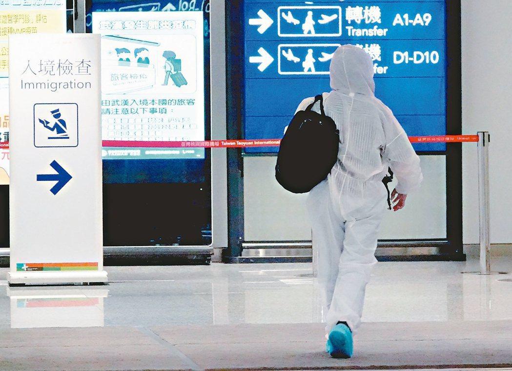 一名搭機入境的旅客,身穿全罩式防護衣通過桃園機場第一航廈入境長廊,準備接受檢疫及...