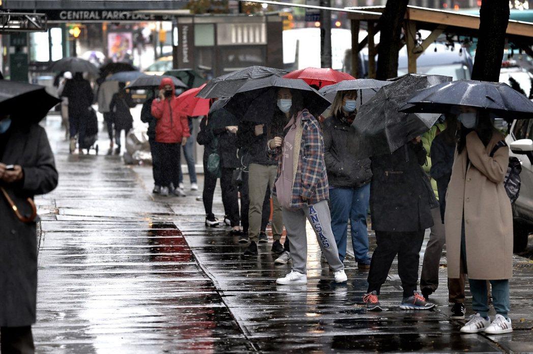 紐約市民13日撐傘排隊,等候進行新冠肺炎快速檢測。歐新社