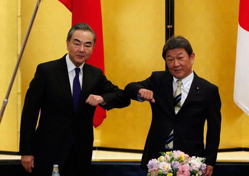 大陸外長王毅(左)廿四日下午抵達日本,並與日本外相茂木敏充展開會談。(法新社)