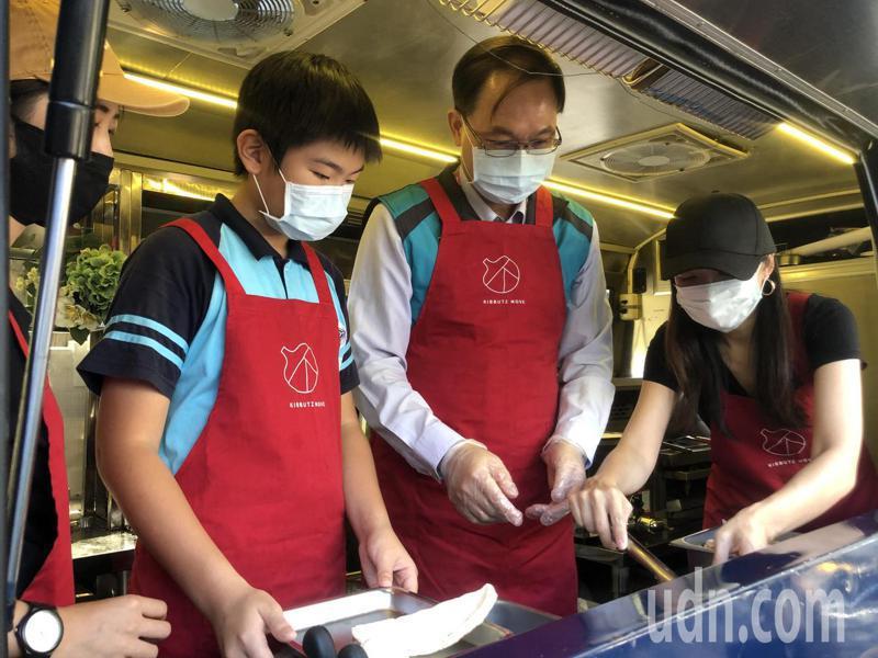 大橋國小學生張祐安(左)與北市教育局主秘吳金盛(中)一同體驗行動餐車作業。記者鍾維軒/攝影