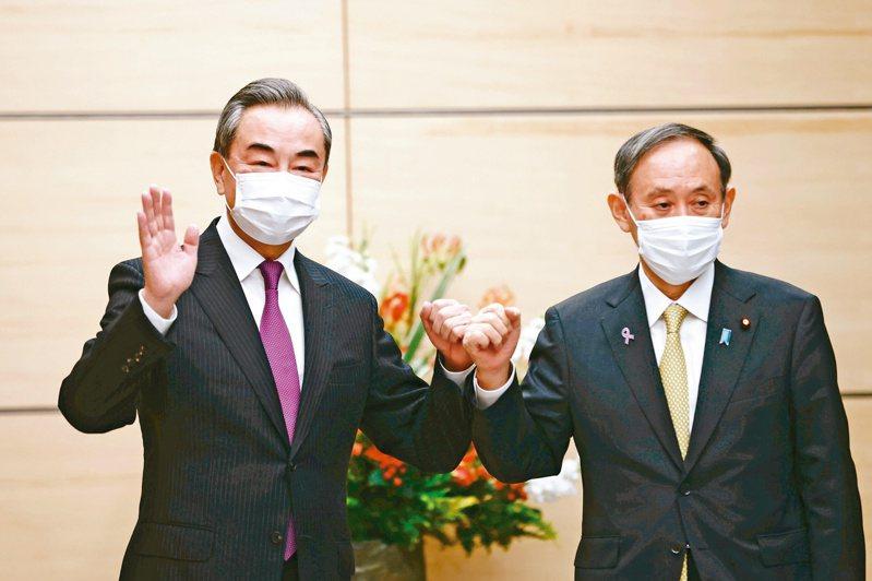日本首相菅義偉(右)昨在東京會見大陸國務委員兼外長王毅(左),兩人對釣魚台議題針鋒相對。(美聯社)