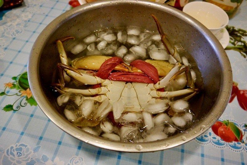 一鍋冰水裡加冰塊和一大湯匙的鹽(鹽可延長冷卻時間),將被綁繩綁著的螃蟹,倒著的直接放在加了冰塊的冰水,蓋過蟹身,讓螃蟹安安靜靜的躺在冰水裡,很快的就凍暈,大約十分鐘,螃蟹沒了活力,就可以了。