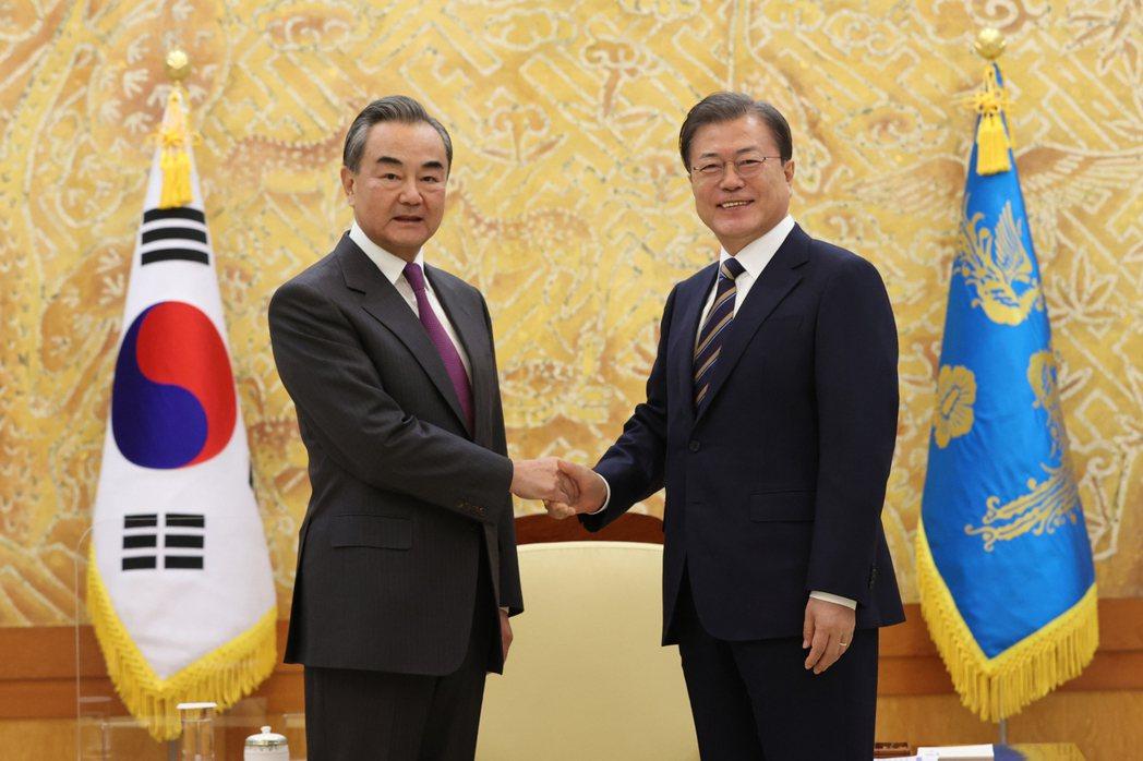 韓國總統文在寅(右)26日在青瓦台接見來訪的大陸外長王毅。美聯社