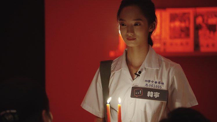 飾演「學姊」的韓寧,突然從黑暗中手持蠟燭驚悚突襲派對。圖/Netflix提供