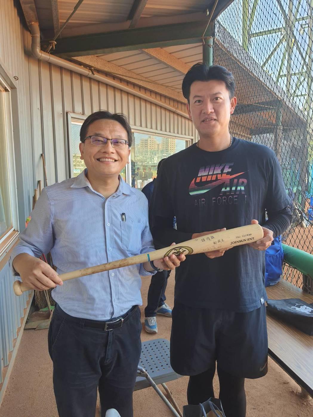 王牌投手王建民(右)贈簽名球棒予崑大行政副校長鐘俊顏(左)。 洪紹晏/翻攝