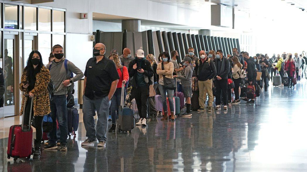 25日美國猶他州鹽湖城國際機場,民眾大排長龍準備搭機旅行。(美聯社)