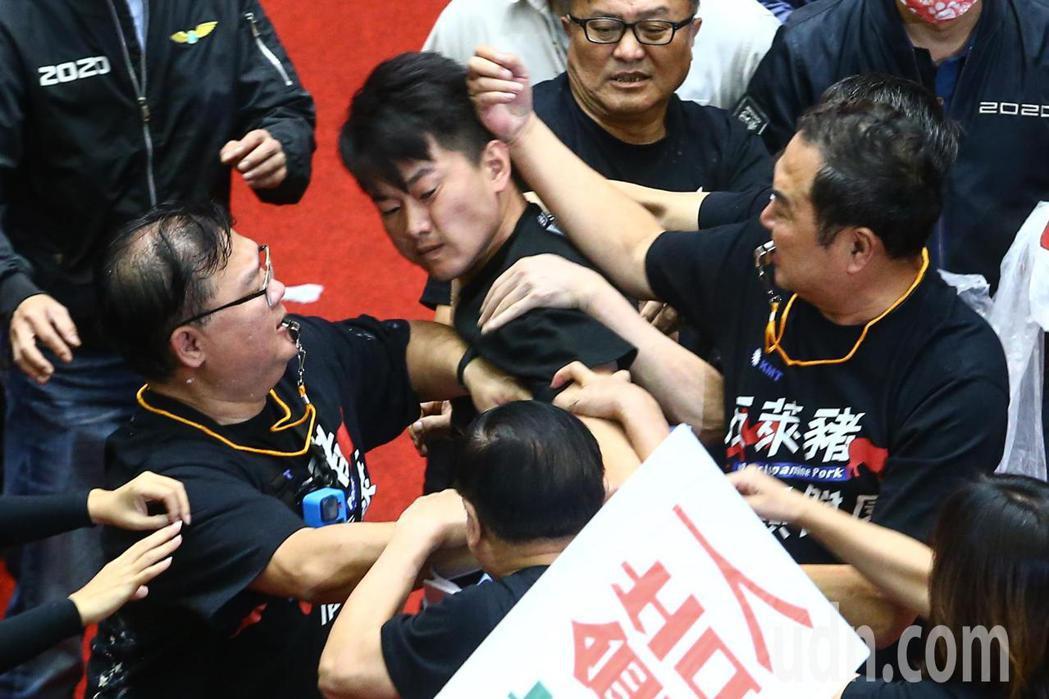 國民兩黨上午在議場內針對萊豬議題進行攻防戰,立委陳柏惟(中)把鄭天財摔到地上後遭...