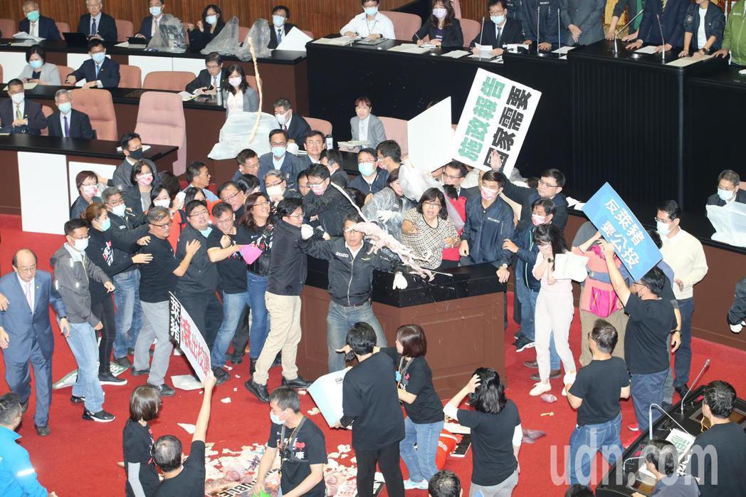 立法院上午進行院會,行政院長蘇貞昌在民進黨立委的保護下上台報告,國民黨立委不滿民...