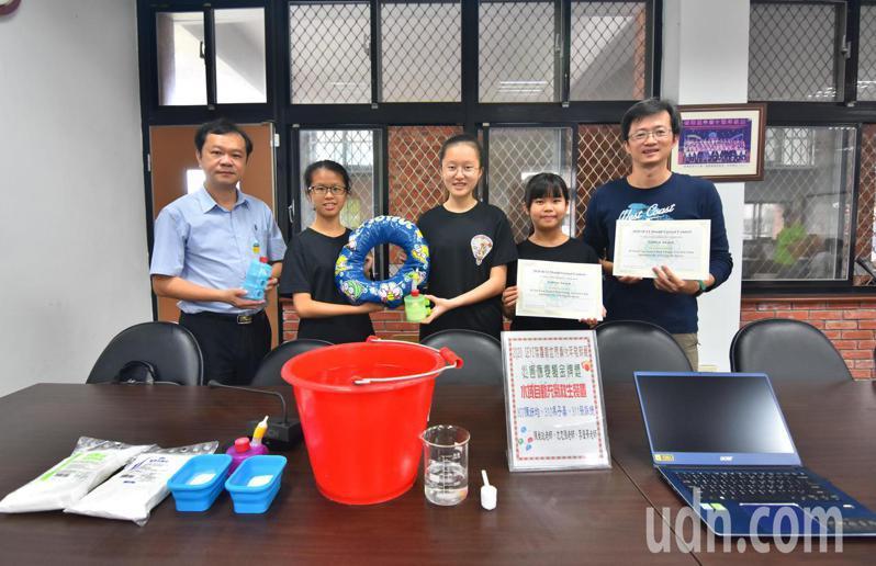 國華國中學生陳妍均(右二)、馮子晏(左二)、張詠捷(中)設計的水域自動充氣救生裝置,摘下世界發明展金牌。記者張議晨/攝影。
