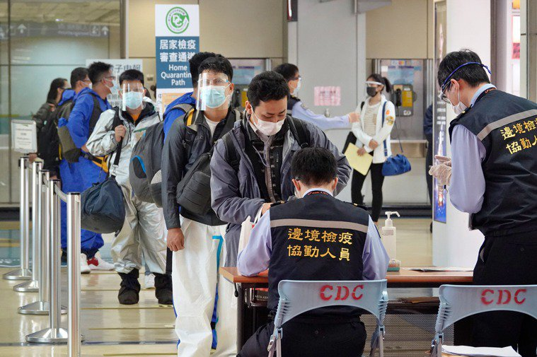 我國再新增9例新冠肺炎境外移入個案,圖為旅客昨天在桃園機場排隊等候集中核實入境電...