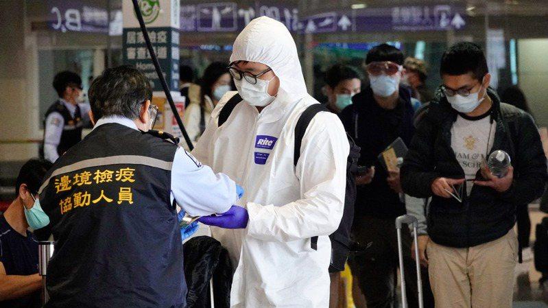 國內多位專家指出,陰性證明雖可擋掉一些病毒陽性者入境,但仍建議指揮中心對在檢疫期滿時全面再採檢一次。圖為旅客穿著全套防護裝備入境。聯合報系資料照片/記者鄭超文攝影