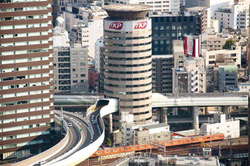 位於大阪阪神高速公路梅田出口附近的一棟圓形建築物,剛好被高速公路正面穿過,形成大阪街景中的一幅奇特畫面。這棟大樓名稱叫「門塔大廈」(TKP Gate Tower Building),是由出租會議室的大型業者TKP所管理的地上16層建築物,內有34間會議室。 圖/翻攝自Forbes