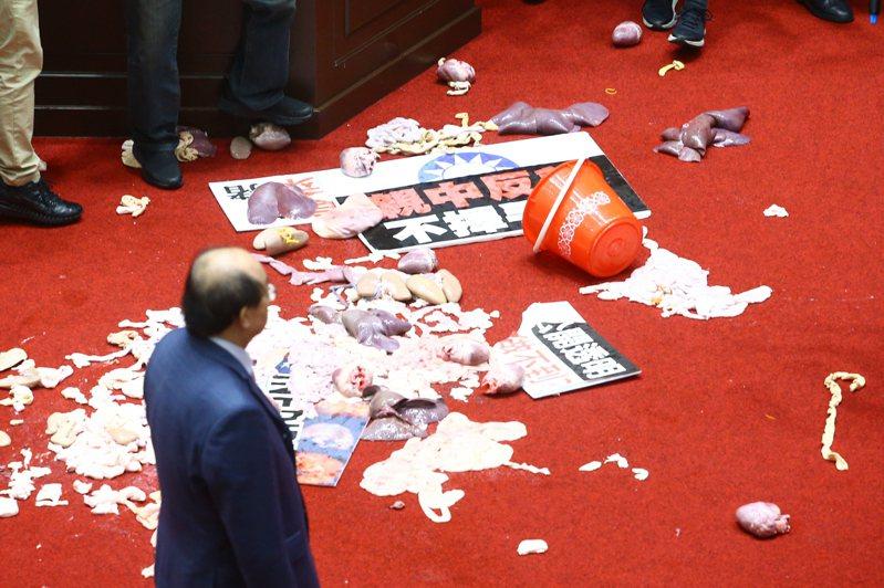 國民兩黨在議場內針對萊豬議題進行攻防戰,行政院院長蘇貞昌上台報告時遭國民黨立委潑豬內臟。記者葉信菉/攝影