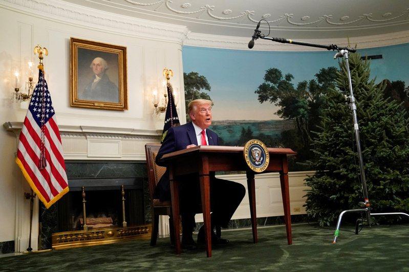 美國總統川普在感恩節當天,坐在一張小桌子後面開記者會。路透