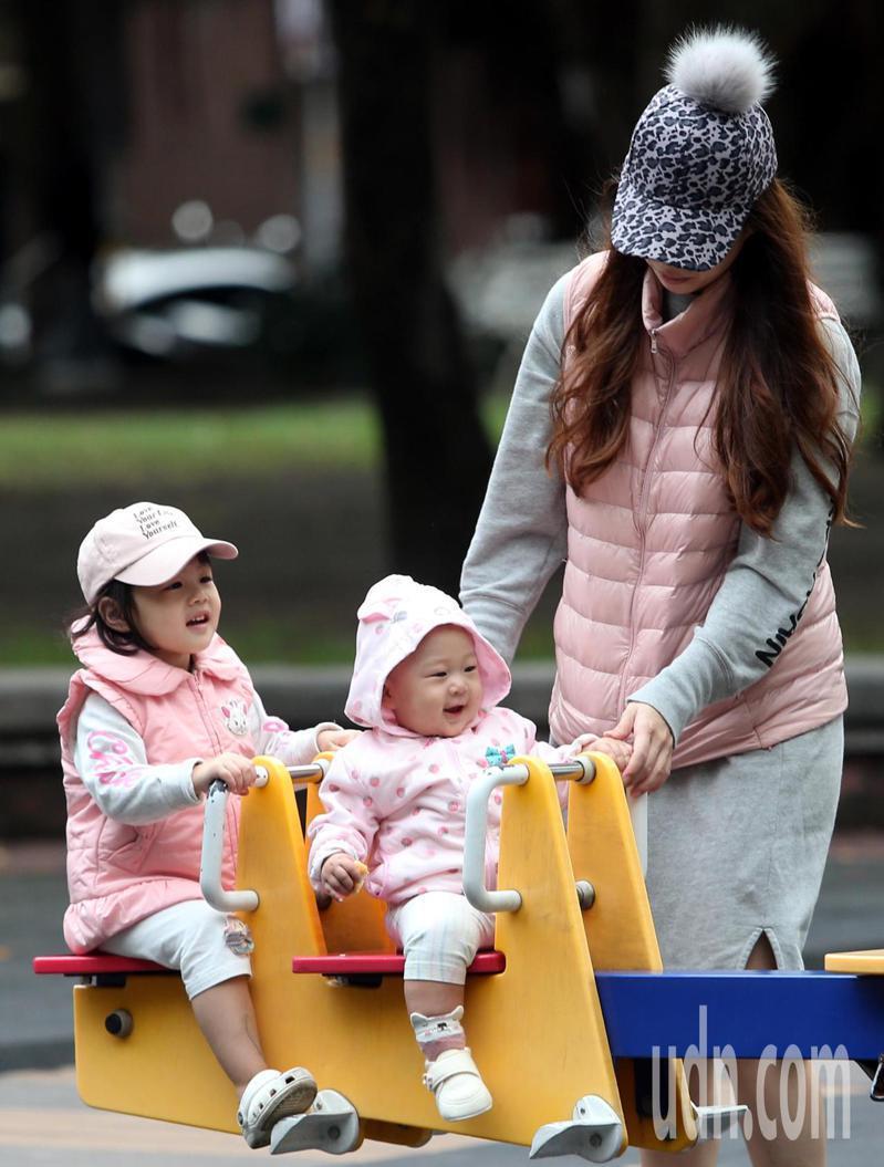 今天雨勢稍緩,不過東北季風威力增強,氣溫明顯下降。涼颼颼的周末,一對穿著同色系保暖童裝的幼兒,玩起公園內的遊具時,展露純真可愛的笑容。記者侯永全/攝影