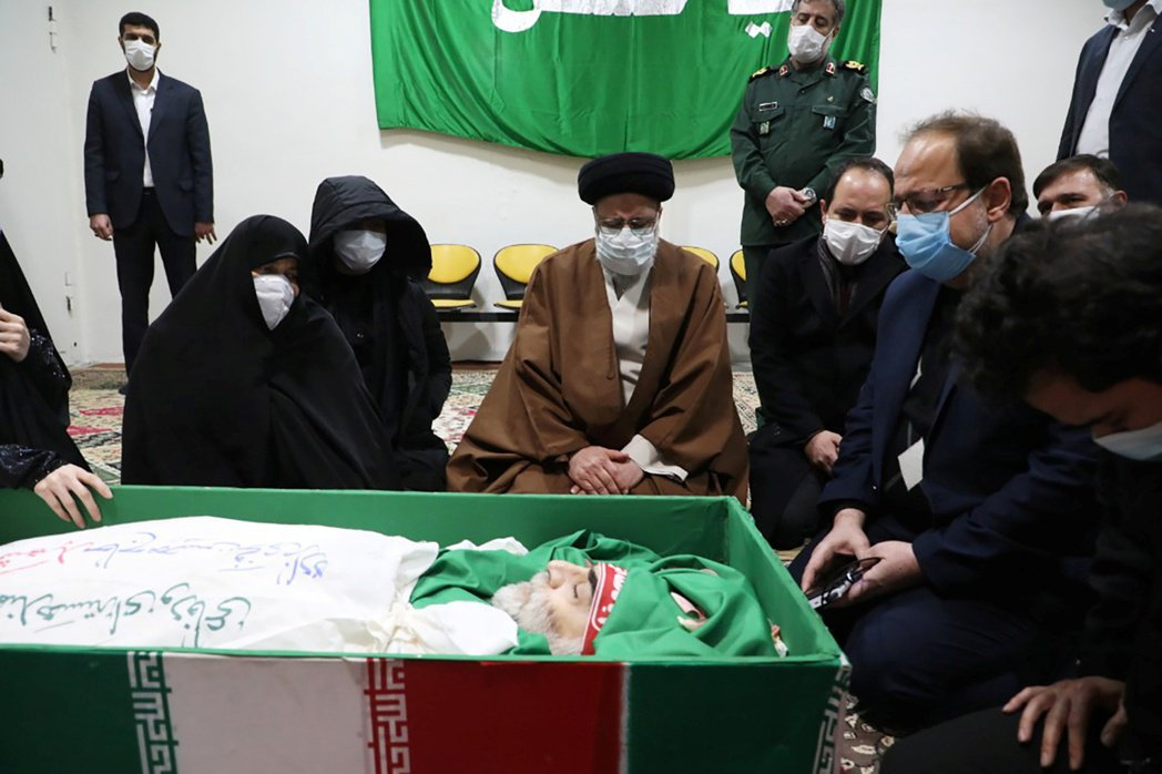伊朗司法部長萊希(Ebrahim Raisi)與法赫里薩德的家屬神情哀傷地跪坐在...