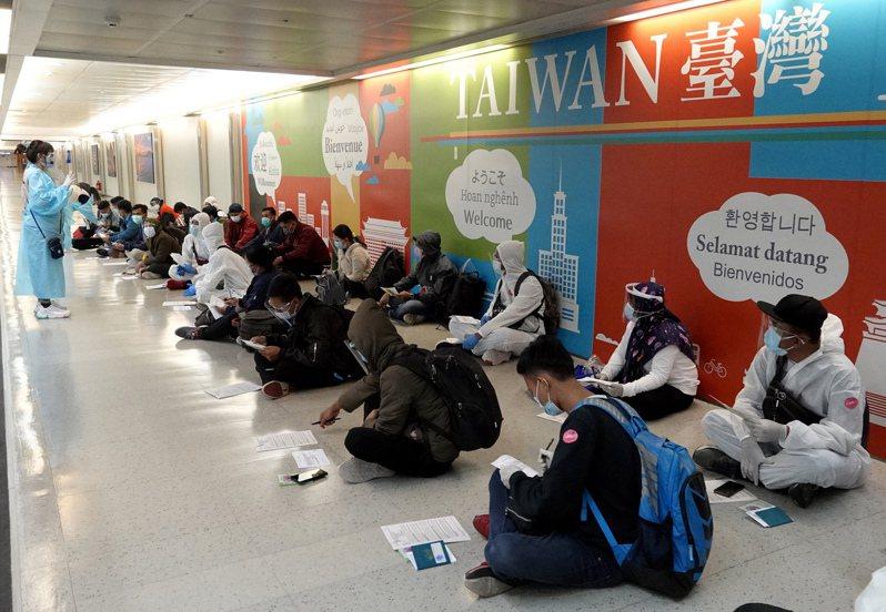 印尼移工等待檢疫 近期印尼移工入境後確診者眾多,圖為昨夜印尼移工入境時,在勞動部官員及檢疫官帶領下接受檢疫,辦理入境手續。記者陳嘉寧/攝影