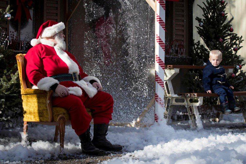 加拿大安大略省京士頓市一歲半的小男童雷克萊爾,廿八日坐在長凳上保持社交距離和耶誕老人拍照。(法新社)