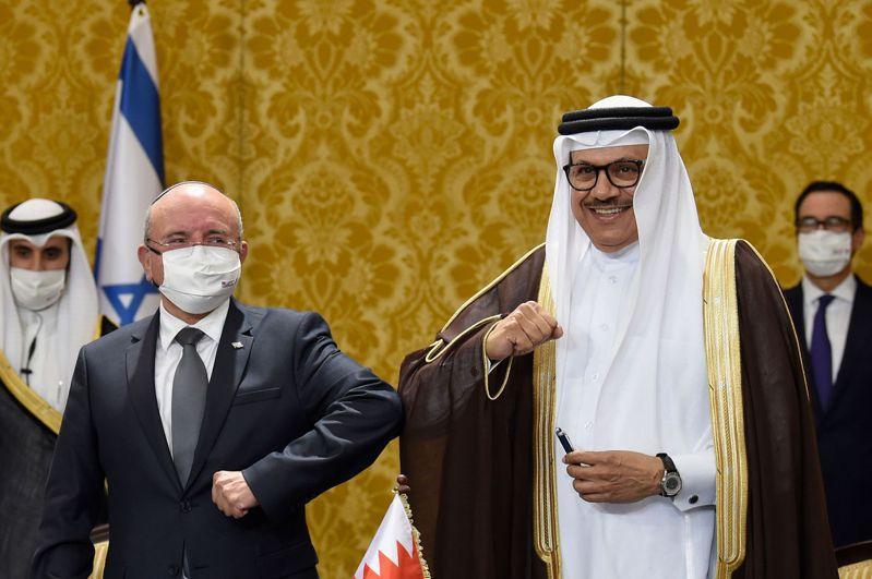 中東局勢已今非昔比,以色列開始與阿拉伯國家建交。圖為以國國安顧問沙巴特(左)與巴林外長札亞尼10月18日在巴林首都麥納瑪的兩國簽署建交公報儀式上,以互碰手肘取代握手。法新社