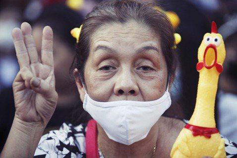 一名婦女拿著塑製黃色小鴨,豎起三指表達訴求。 圖/歐新社