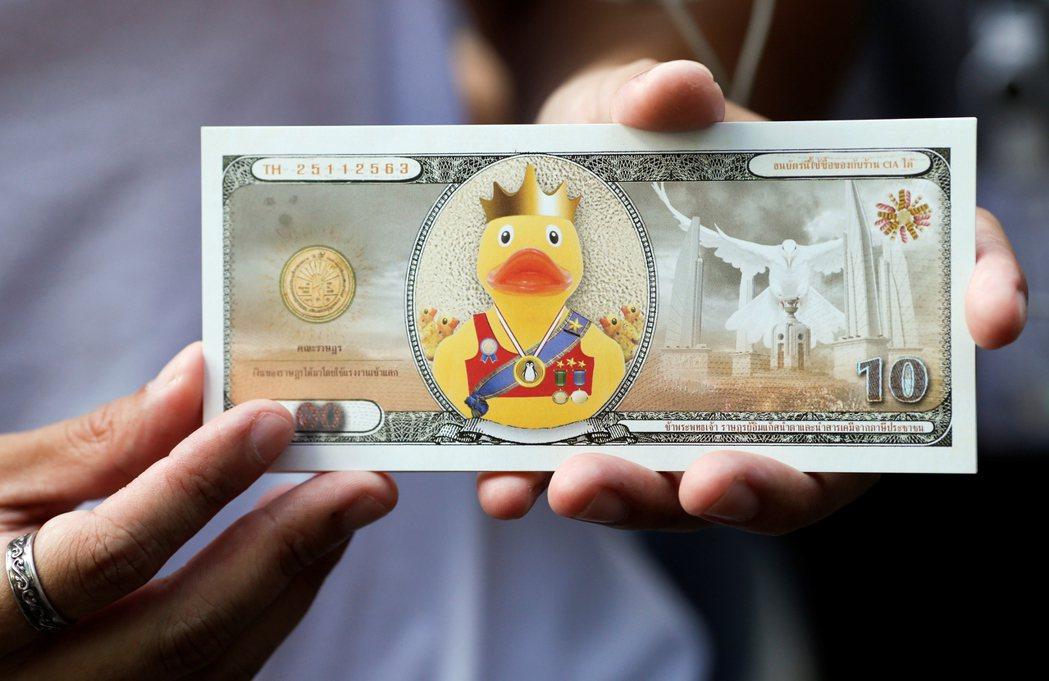 示威者拿著印有黃色小鴨的假鈔,要求泰王將資產歸還給人民。  圖/路透社