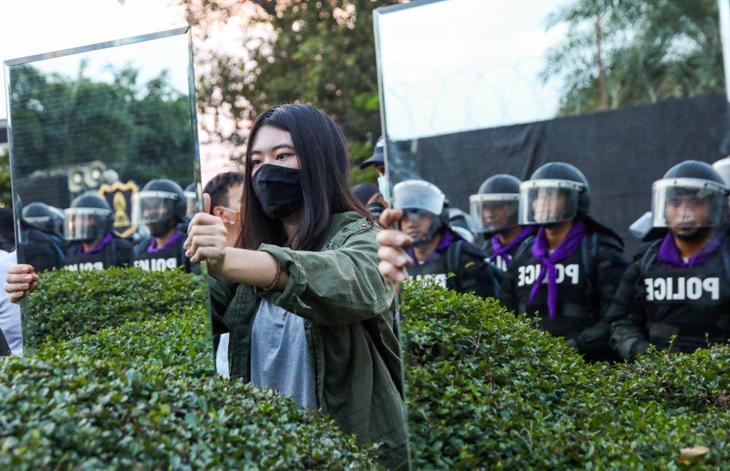 示威者在警察面前舉起鏡子,要求王室改革。 圖/路透社