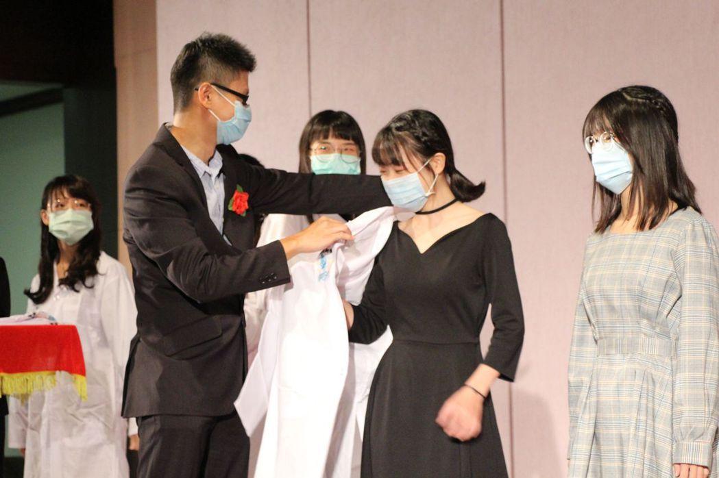 「醫技系」授袍典禮上,指導老師為實習生一個個披上白袍。 義守大學/提供