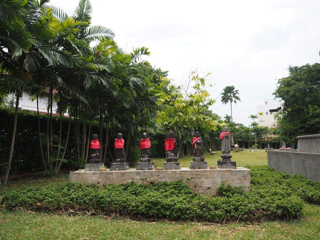 日本人墓地公園大門左側立著一排圍著紅巾的小石像。