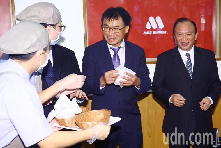 陳吉仲(右二)與林聰賢(右一)在記者會上吃國產豬肉的漢堡供媒體拍照,拍完照後主辦...