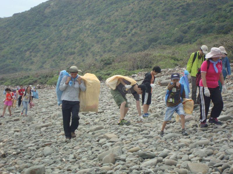 墾丁國家公園南仁山生態保護區出風鼻海岸淨灘工作假期,遊客要步行1個小時到海邊撿海漂垃圾,有人樂此不疲,年年揪團參加。圖/墾管處提供
