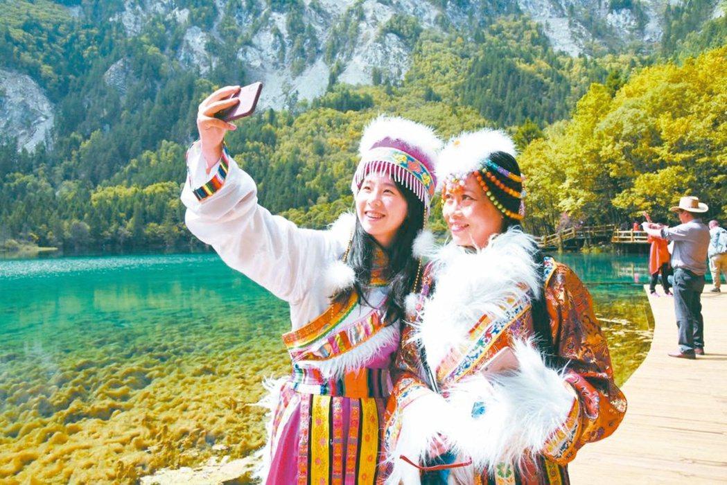 九寨溝五花海前,遊客歡喜拍照。 圖/本報四川阿壩州傳真