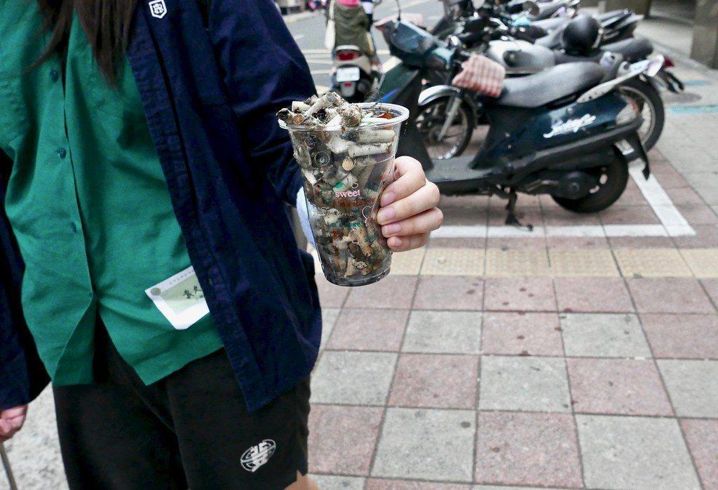 即使環保局前一週清潔過,菸蒂數量仍相當可觀,馬上就「集滿」一杯。 圖/鄒敏惠...