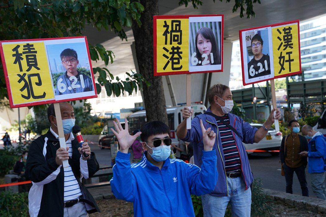 12月2日,在法庭外反對眾志三子的民眾。在入獄判決結果公布後,還有反對者故意拍手...