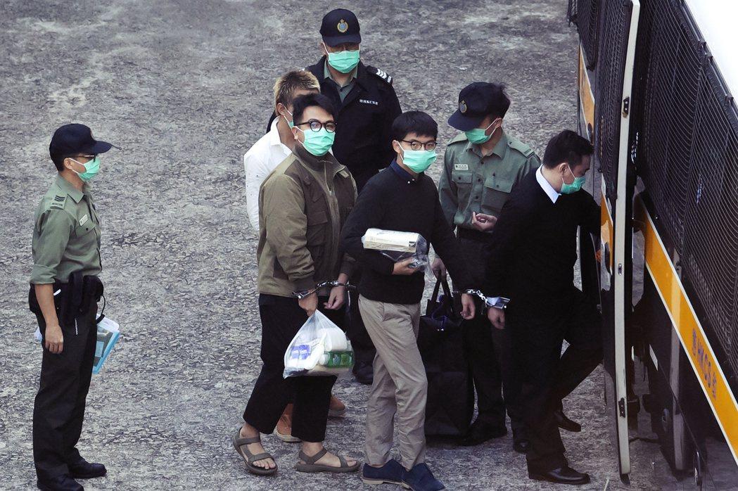 12月2日,林朗彥(左)與黃之鋒(中)被押出庭聽判。 圖/歐新社