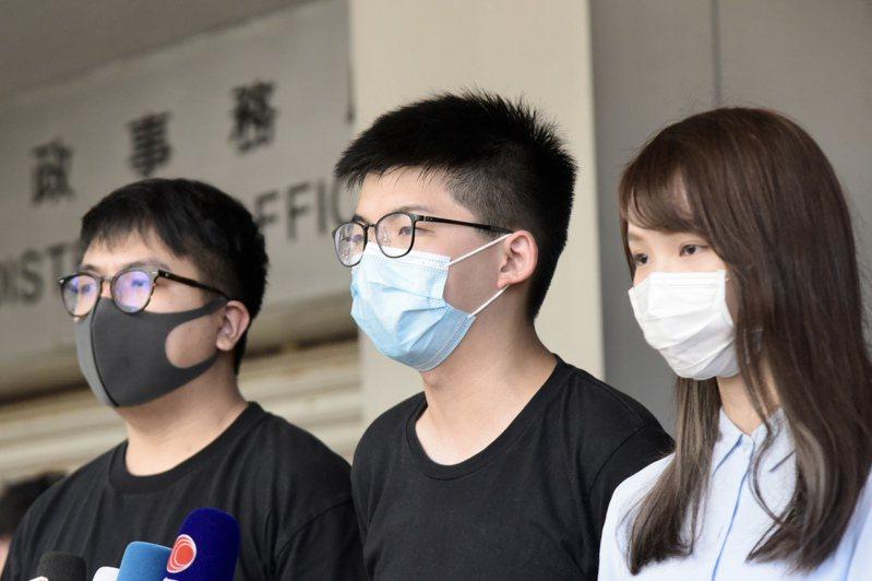 前香港眾志成員黃之鋒(中)、林朗彥(左)、周庭(右)涉嫌參與去年6月21日包圍警察總部事件,被控以煽惑他人明知而參與未經批准集結、組織未經批准集結,以及明知而參與未經批准集結三項控罪。香港中通社
