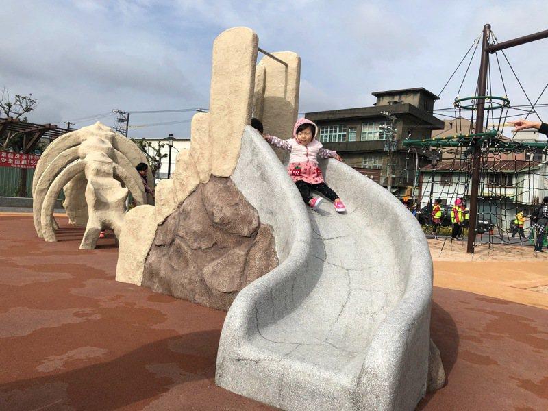 恐龍造型的溜滑梯極具特色,孩子們在上方玩得不亦樂乎。圖/新北市工務局提供