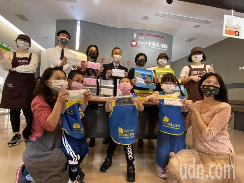 台中口罩業者釩泰口罩公司總經理李國鈺(後排中)將義賣口罩所得1成,捐給瑪利亞愛心學園籌設快樂襪工廠。記者趙容萱/攝影