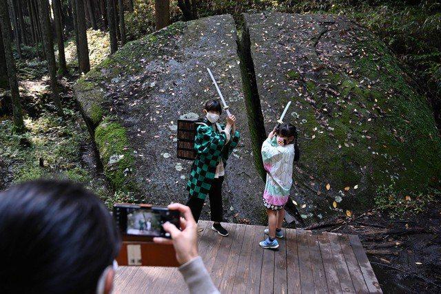 裝扮成《鬼滅之刃》登場人物的孩子們,在巨石前開心拍照。圖/朝日新聞中文網提供