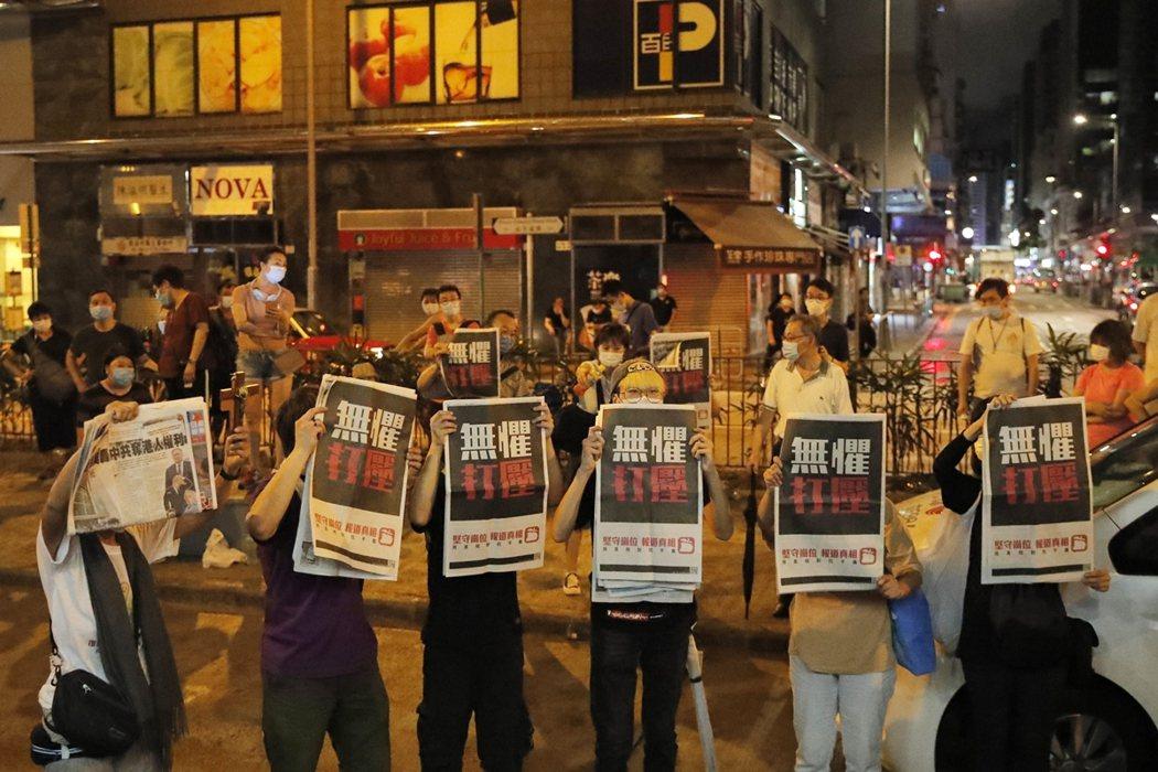 圖為今年8月12日,有人手持蘋果日報聲援黎智英。 圖/美聯社